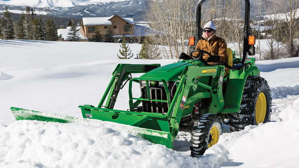 Person driving 3e utility tractor in the snow